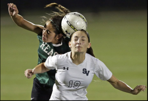 The Rattlers' Gaby Galan (left) comes in to disrupt a header catch by the Rangers Kaitlyn Bumbarner as the Reagan girls beat Smithson Valley 1-0 in third round 6A soccer playoffs at the UTSA Park West Complex on April 7, 2015.