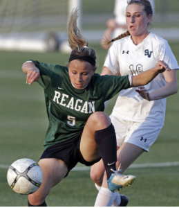 The Rattlers' Sam Batley works the ball in front of Brooke Cousins as the Reagan girls beat Smithson Valley 1-0 in third round 6A soccer playoffs at the UTSA Park West Complex on April 7, 2015.