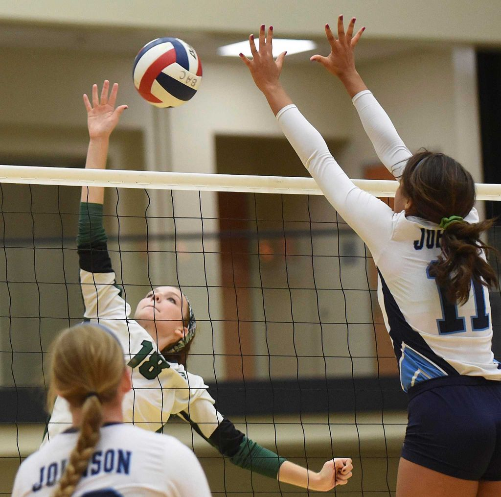 Lauren Schilling of Reagan (18) and Adonica Wright (11) of Johnson battle at the net during volleyball action at Littleton Gym on Wednesday, Sept. 16, 2015.
